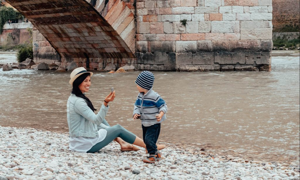 Mother and son sitting near the bridge in Verona Italy wearing nomad's clothing